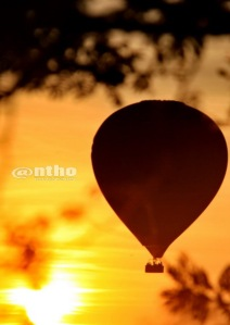 Silhouette of hot-air balloon while sunrise